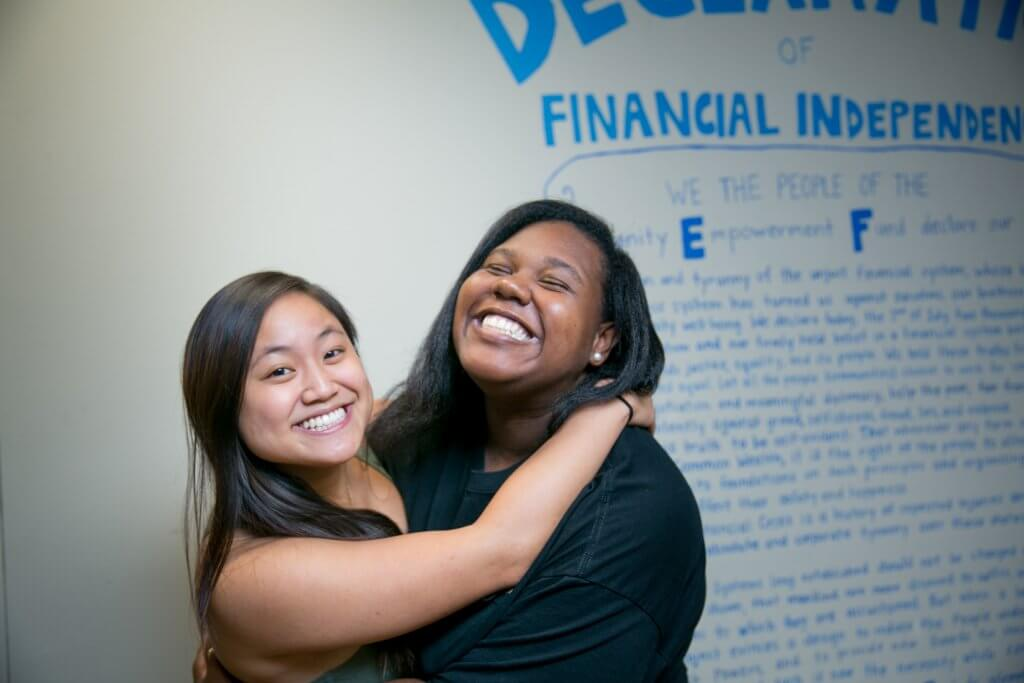 "Two women hug and smile in front of a white wall that states the ""Declaration of Financial Independence of the Community Empowerment Fund"" in blue handwriting."